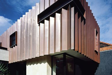The addition's pleated copper facade complements the tones of the existing red brick Federation house.