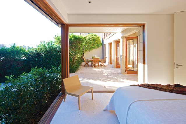 Sliding glass doors in bedroom embrace the garden beyond.
