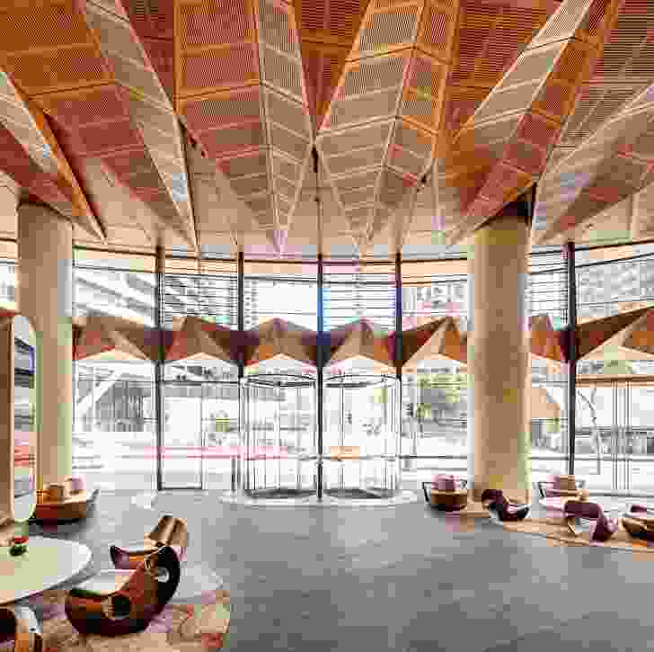 """The marine plywood canopy evokes a """"line of trees along the edge of the shore,"""" undulating above the lobby."""