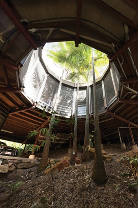 The dodecagonal house wraps around a central vertical garden of palms and bamboo.