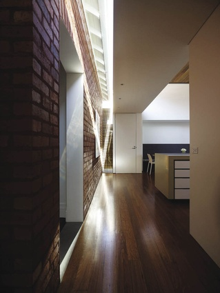 The extension is attached to the existing house by a strip of glazing, allowing light to penetrate onto the brick wall.