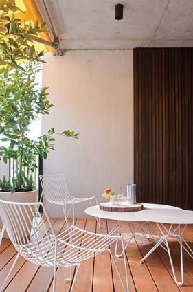The large balcony features a lemon sail awning and potted lime trees.