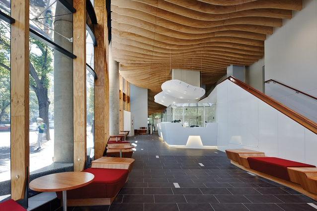 An undulating ceiling of plywood is a sculptural addition to the foyer space.