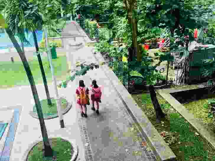 Children in Singapore, walking to school through the neighbourhood community gardens.