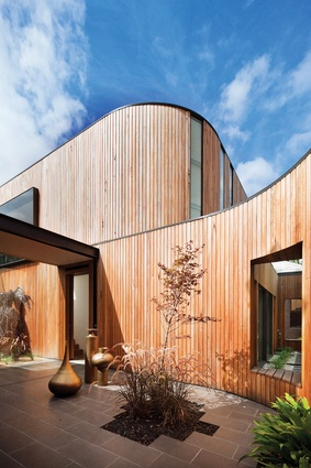 Timber-clad forms curve around to enclose protected exterior spaces at Kooyong House.