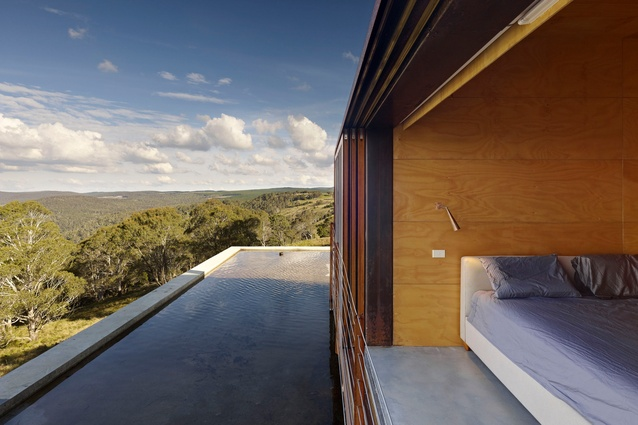 On the upper level and housed within one of two steel boxes, this bedroom can be opened to the elements.