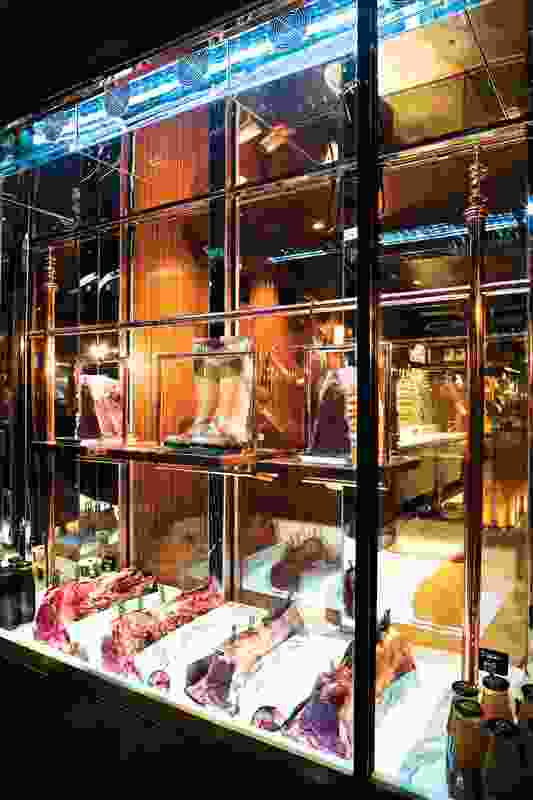 Glass cabinets, similar to museum vitrines, display cuts of meat.