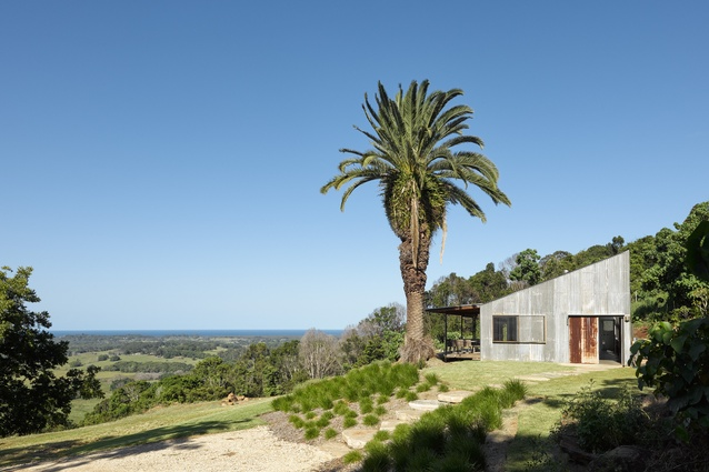 From the forest the house presents as a simple, silvery grey trapezoid, its a roofline in tune with the tumbling slope.