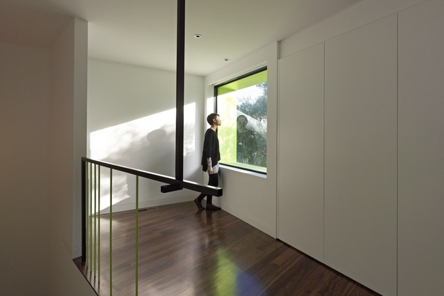 The upstairs landing sports two details: a window framing a tree outside and a signature balustrade detail.