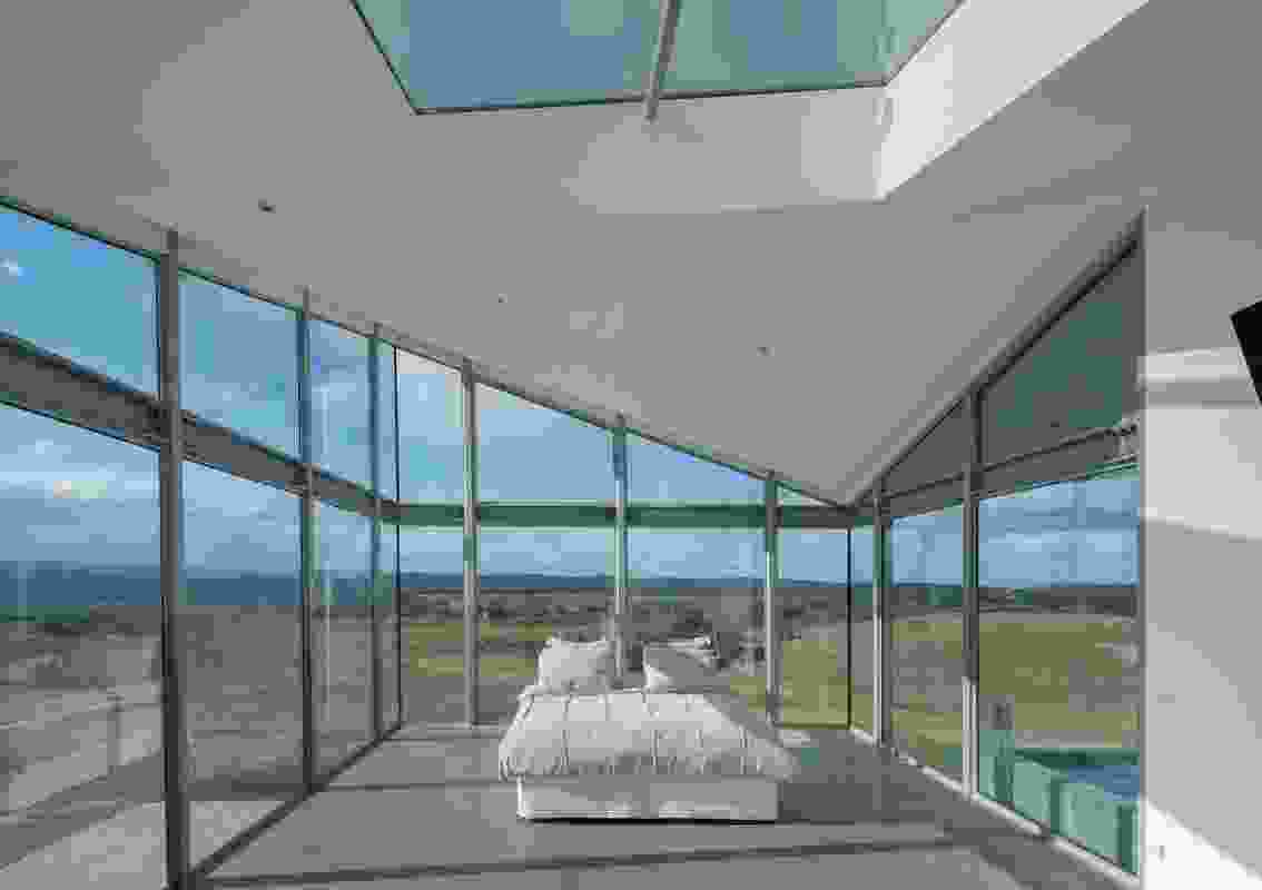 Enclosed on three sides by glass, the main bedroom rises to almost double height, punctuated by a skylight.