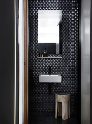 Texture and sophistication is carried through all spaces of the apartment, including the bathroom.