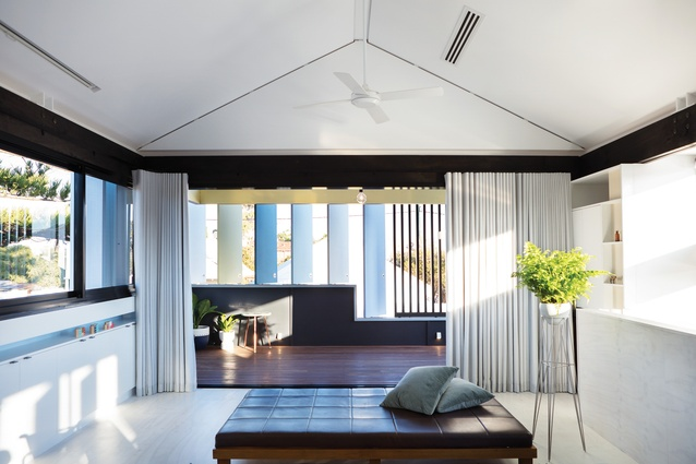 The black-and-white interior is softened by sculptural grey curtains and the muted colours of the outdoor shutters.