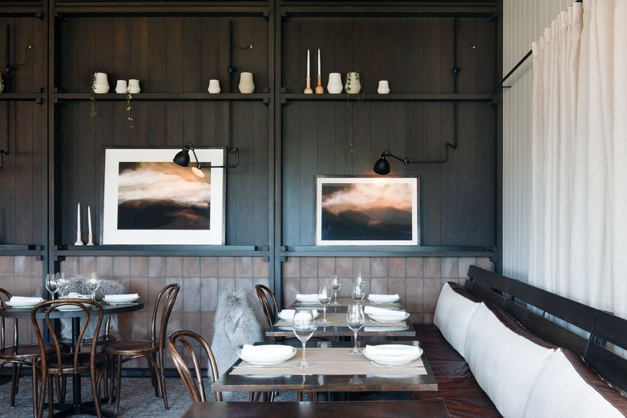 The dining room's panelled wall displays artwork and vases, while the lower section is finished in warm brick tiles. Artwork: Rebekah Stuart.