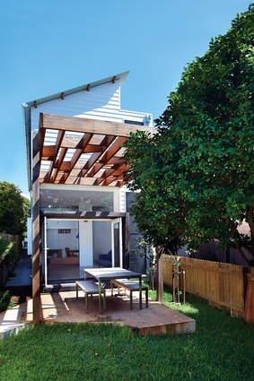 A concrete platform extends living area out under a pergola.