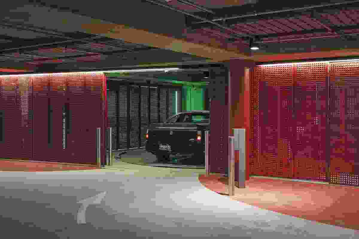 In contrast to the icy-white exterior, Geyser's underground car park is nightclub-like in pillar-box red with neon lighting. A 'robotic' 165-car stacking system whisks cars away into a compact space devoid of human activity.