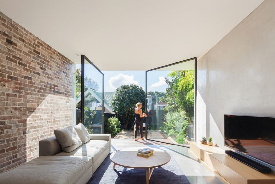 Two full-height pivot doors define the living zone and frame the view to the terraced garden.