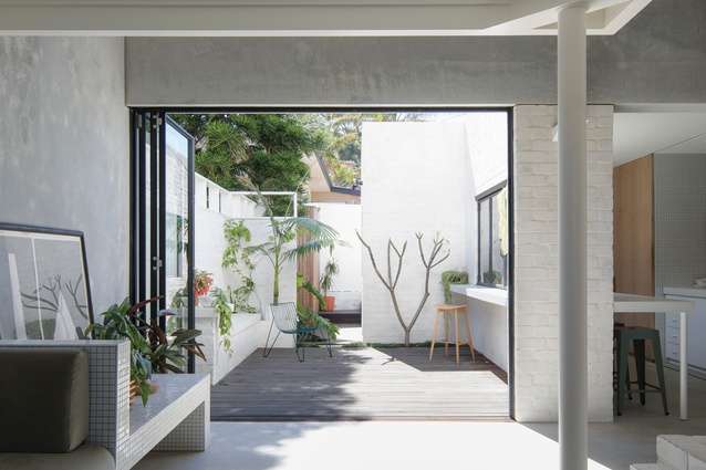 The kitchen and living spaces open to a sunny courtyard that works with the high ceilings to counter the dwelling's diminutive footprint.