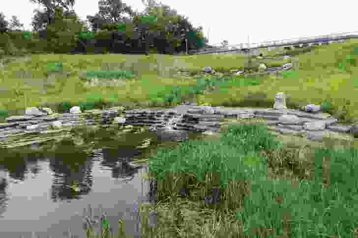 A stream rushes over recycled concrete slabs into the lake at Henry Palmisano Park.