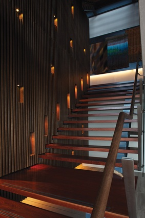 A wall of timber battens with recessed lights flanks a staircase in the main building.