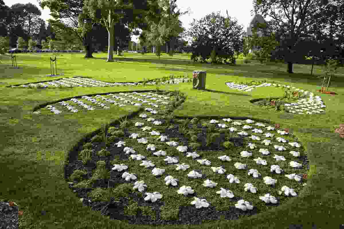 Three free-form garden beds hold a repetition of flower-shaped pavers.