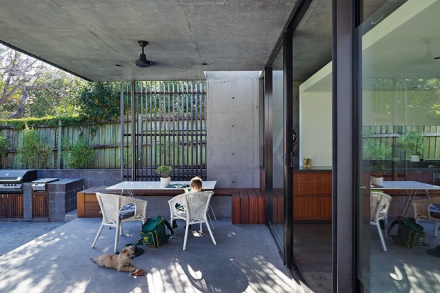 A barbecue terrace sits adjacent to the kitchen, covered by a roof in unfinished concrete.