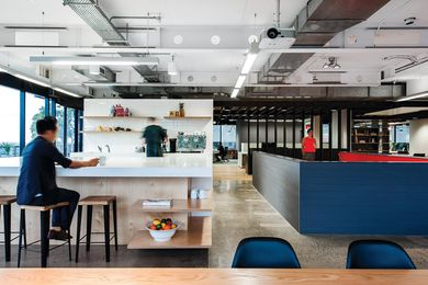 The office's kitchen features a monolithic kitchen bench, with views to Sydney harbour.