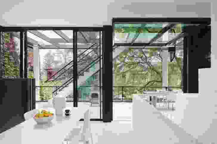 After climbing the first flight of stairs and turning right towards the kitchen, a glimpse of the bay is offered through the pergola, partially obscured by the elevation of the external stair.