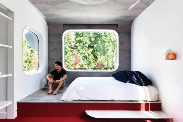A cantilevered bedroom with distinctive round windows pops out over the title line, announcing itself to the street.