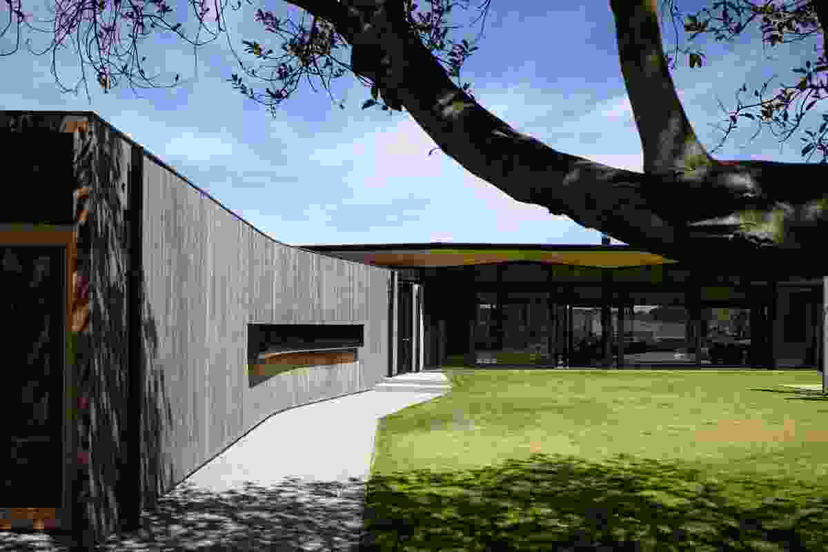 A sheltered flat lawn area contained within the U-shaped plan.