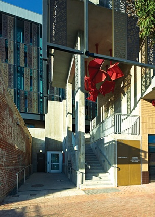 A red, folded and perforated steel lamp hangs in the entry off Newcastle Street.