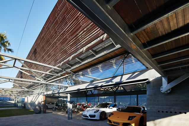 Six large steel trusses that run the width of the site reference the client's involvement in the steel industry. On the ground floor, the glazed garage houses and displays the client's vehicle collection.