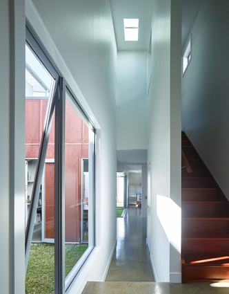 The linearity of the hallway is punctuated by drawing a volume up through the two-storey central pavilion.