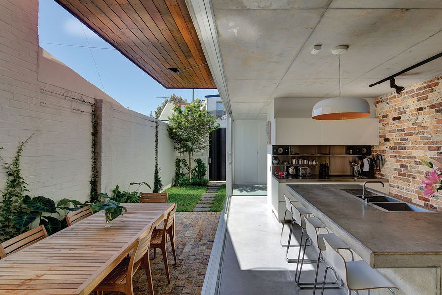 Large glass doors can be slid open to connect the kitchen with the courtyard, creating one large indoor/outdoor room. Artwork: The Misfits poster, United Artist (kitchen).