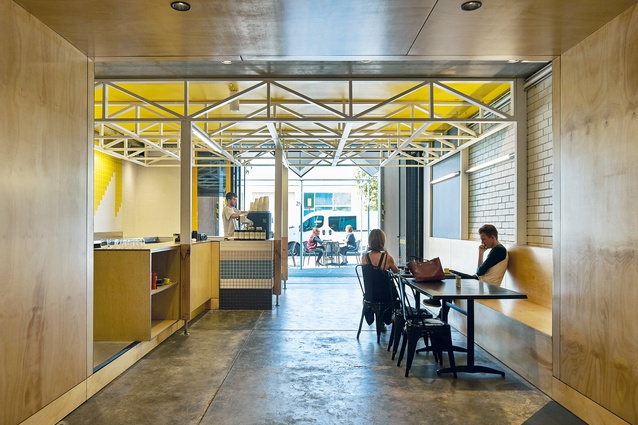 Dr Clause cafe is lined with plywood and punctuated with a trussed bulkhead.