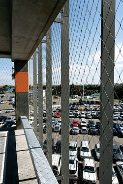 """The single tensioned cable mesh fabric facade allows """"open deck"""" classification for the Sydney International Airport car park, by DesignInc. Image: Martin Van der Wal."""