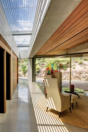 A corridor with a wall of blackbutt cabinetry and a skylight divides the sleeping and bathing zone from a triangulated reclining/art space. Artwork: Coloured vessels by Ben Edols and Kathy Elliott. Vessel on table by Giles Bettison.