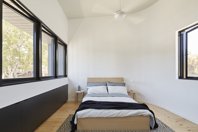 In the bedroom, the ceiling is raked to create a sense of volume in a modestly sized space.