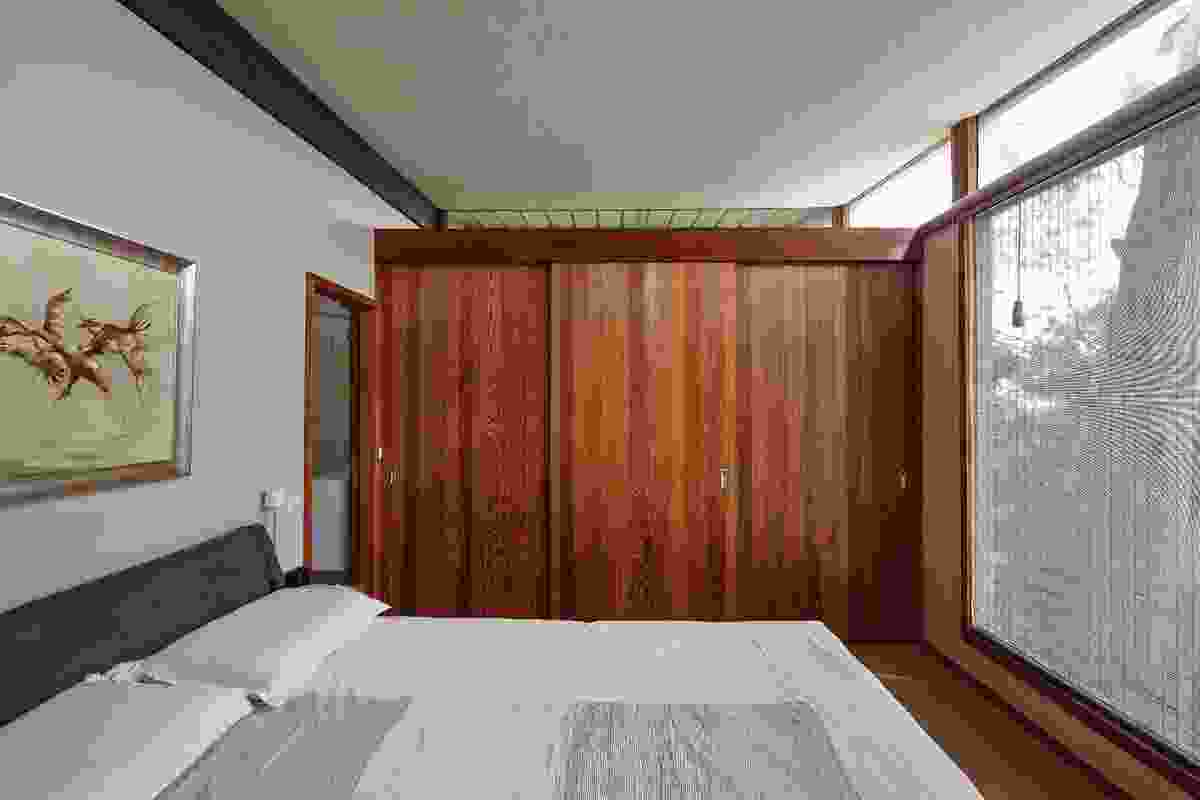Bedrooms are simple and small. Echoes of Japan extend to details such as matchstick blinds and sliding wooden panels to screen clutter. Artwork: Bette Hayes.