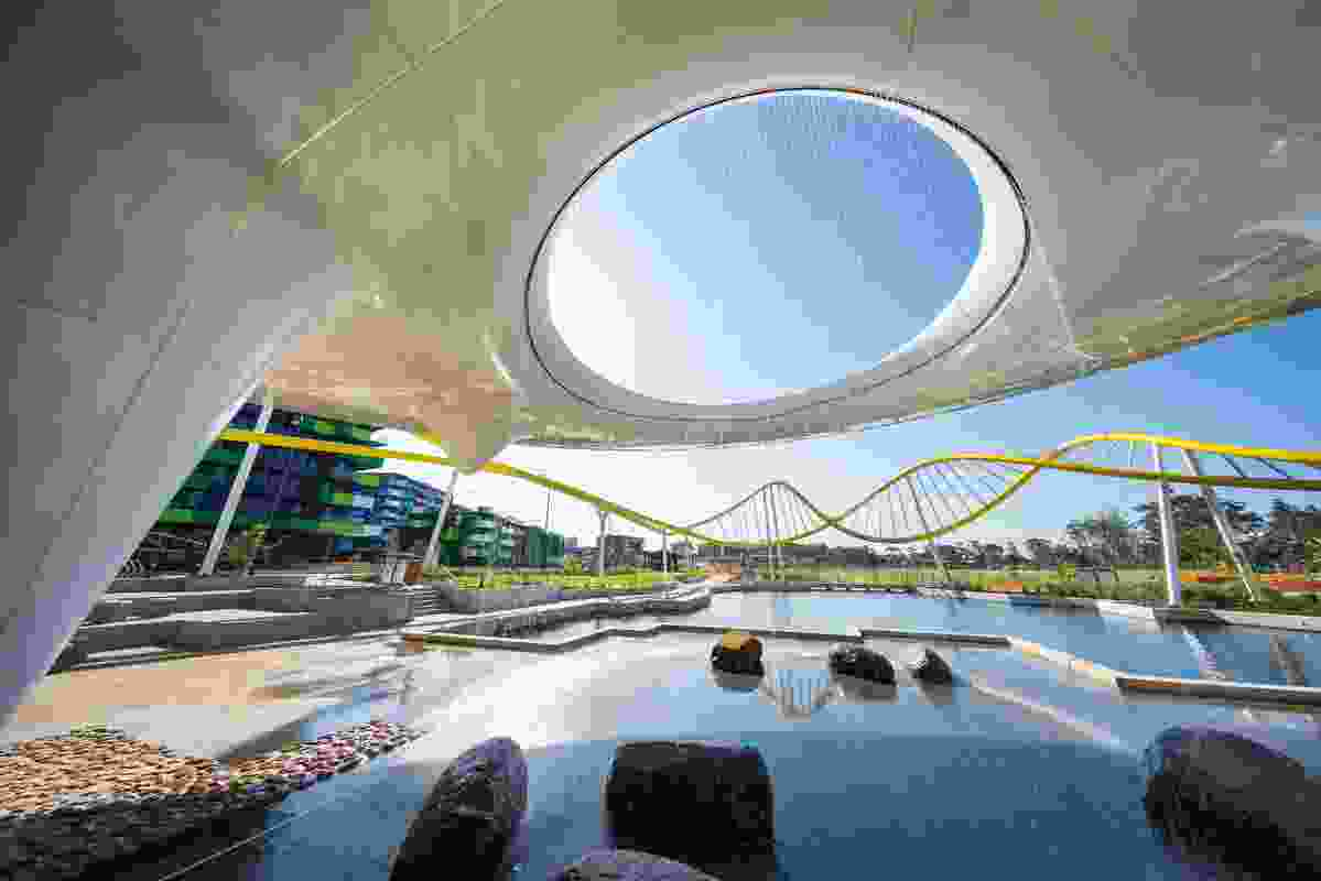 Water cascades through an oculus in the Disc, which offers shade and evaporative cooling, while providing a visual anchor to the Village Heart and main park beyond.