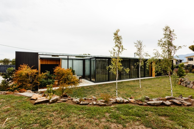 While the house is designed to merge with its landscape, it is also clearly delineated by black framing.
