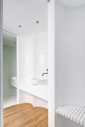 The bathroom comprises an assembly of separate spaces defined by a series of curved walls in white tile.
