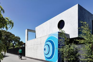 A hand-painted mural by Melbourne artist Lucas Grogan features brightly on the off-form concrete exterior of the house.