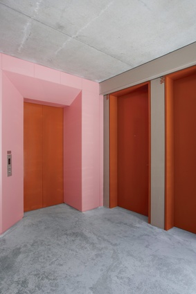 In contrast to the greys of the apartment interiors, colour is explicitly applied in the common spaces, such as orange and pink at the lifts and doorways.