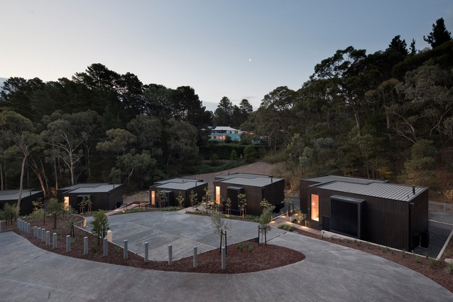 A series of interlocking duplexes clad in black-stained timber.