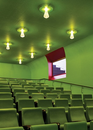 A green auditorium contrasts the clinical laboratory spaces.