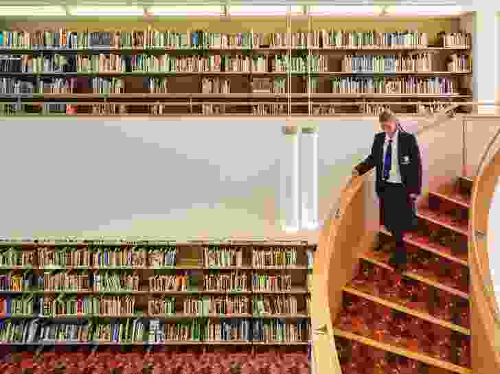 The library rooms are comprised of two-storey volumes connected by sweeping staircases.