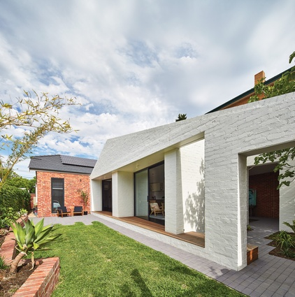 Large glazed openings fold inward, creating deep external niches that invite occupation and offer shade.