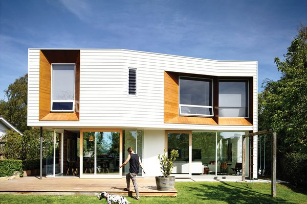 A two-storey extension at the rear of the site adds a solid, weatherboard form hovering above a level of full-height glazing.