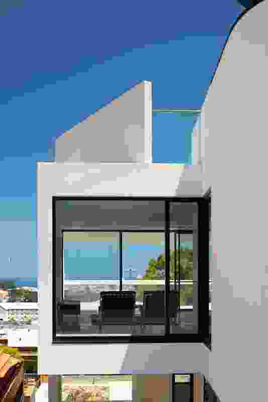 Composed of protruding masses and setback voids, the houses have a sculptural quality reminiscent of work by modernist architects such as Le Corbusier.