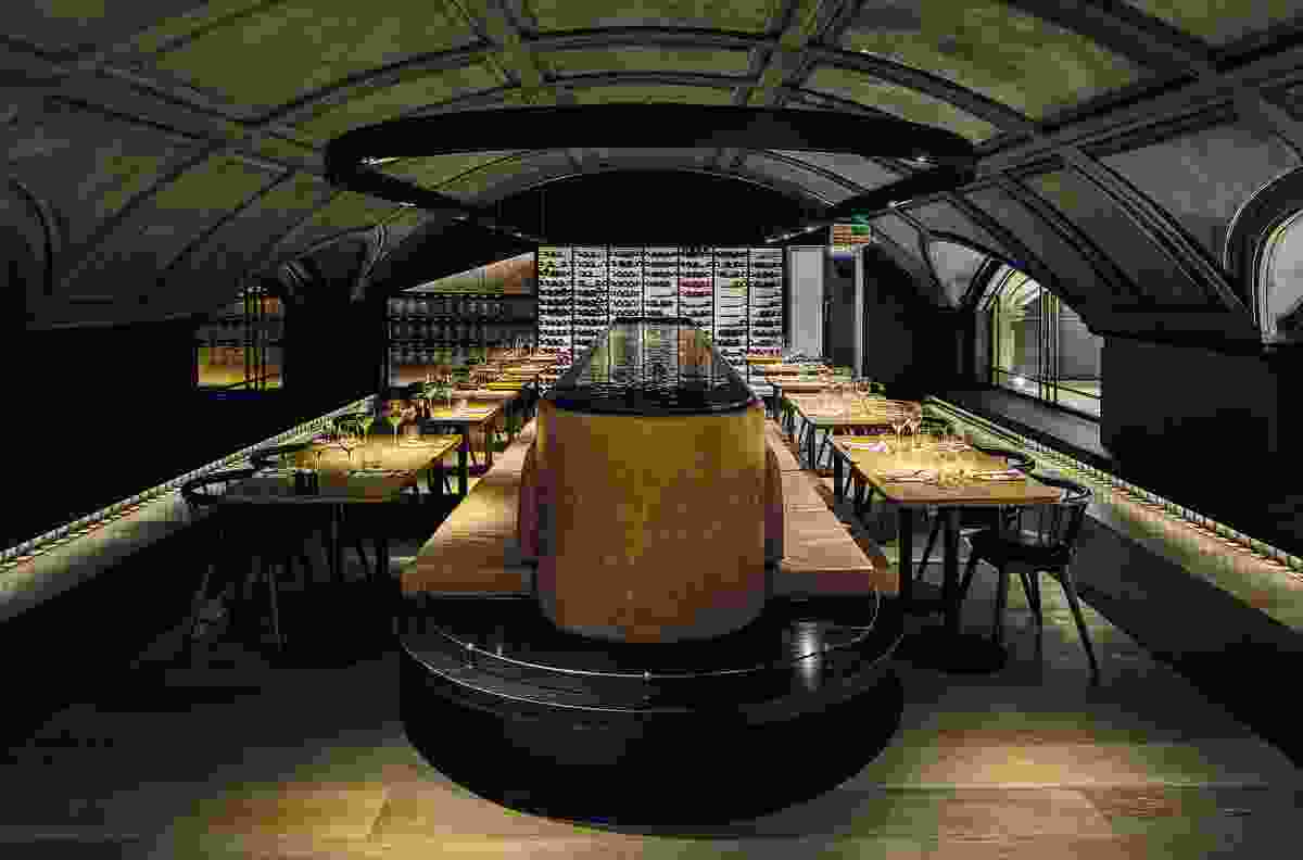 In the distillery bar, hundreds of wine bottles are showcased, illuminated within a faceted wall that flanks the rear of the space.